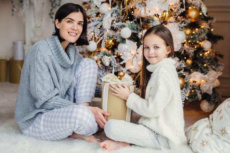 Little child and her mother sit on warm white carpet near decorated New Year tree, holds present in hands, have pleased and happy stock photography