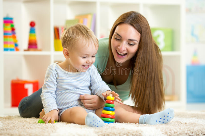 Little child and his mommy playing with toys. Little child boy and his mommy play with toys at home royalty free stock photos