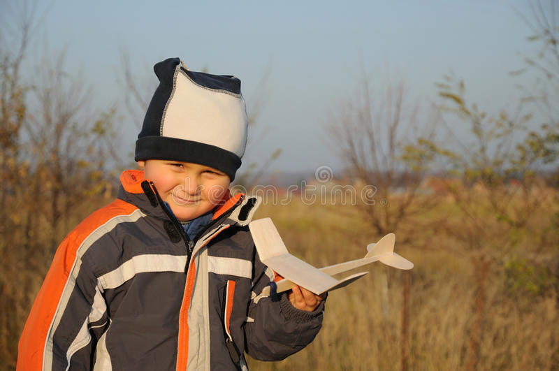 Little child holding plane model. Portrait of a smiling child, little boy, holding a wooden small plane model stock image