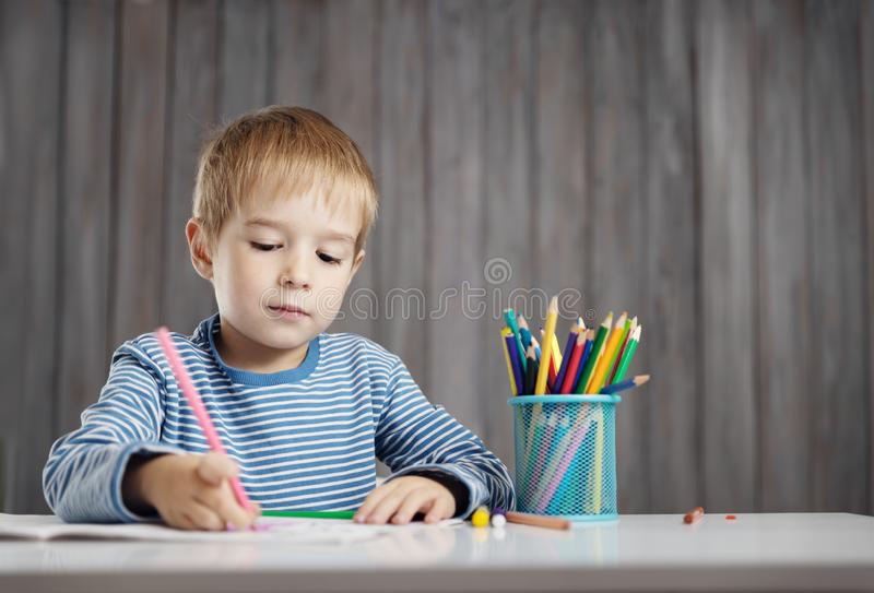 Little child at home drawing on the paper stock photography