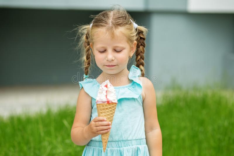 Little child with ice cream on the street. The concept of childhood, lifestyle, food, summer. Little child with ice cream on the street. The concept of stock photos
