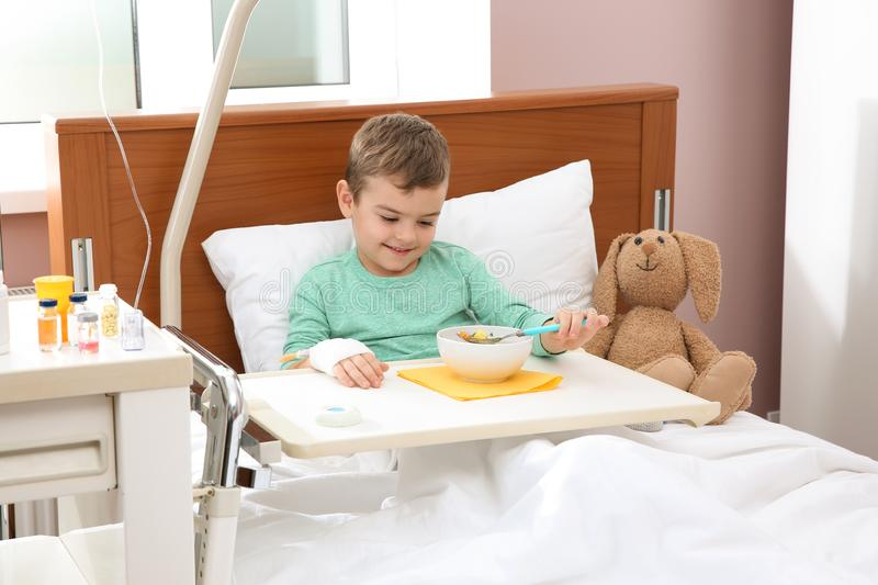 Little child with intravenous drip eating soup in hospital royalty free stock photos