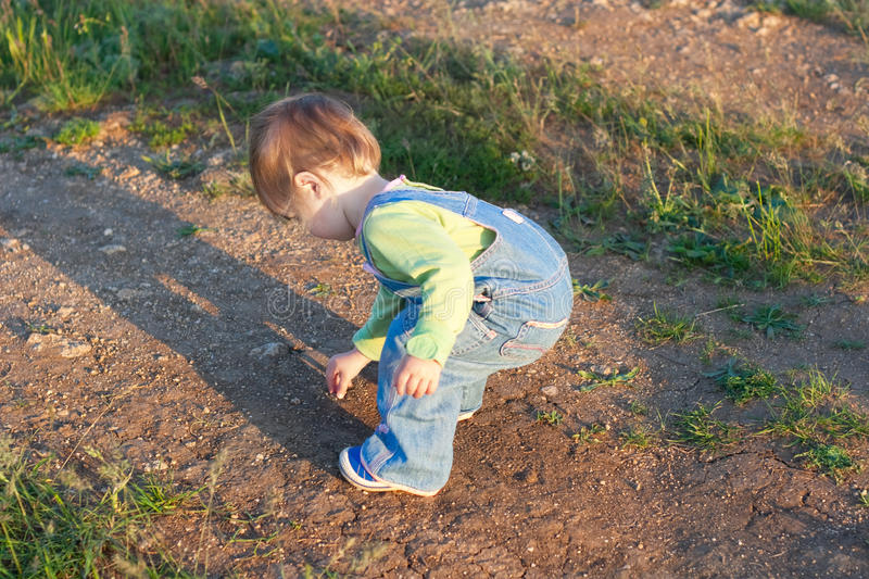 Little child in the jeans coverall pick up stones. On the dirt road royalty free stock photography