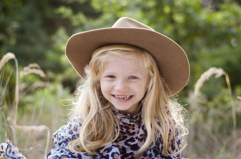 Little child  with long blond hair and hat royalty free stock image