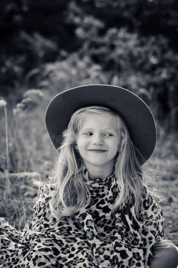 Little child  with long blond hair and hat stock photo