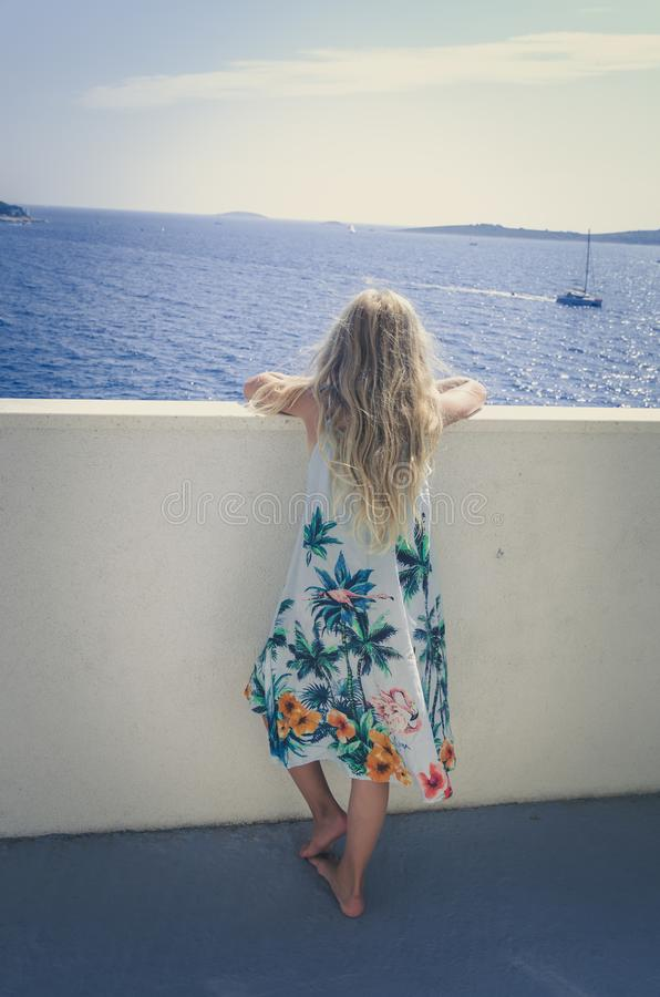 Adorable girl  with long blond hair and summer dress looking from the balcony stock photography