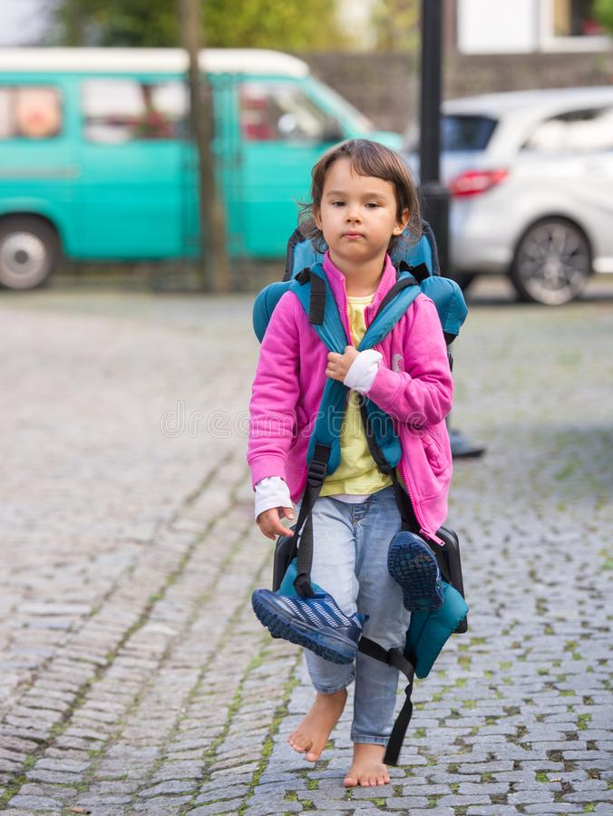 child with luggage back walking on the streets in bare feet royalty free stock image