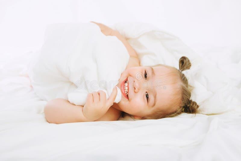 Baby Girl Lying On White Sheet On The Bedroom Stock Photo