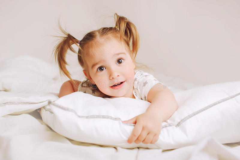 Naked Surprised Baby Girl Lying On White Bed Stock Image