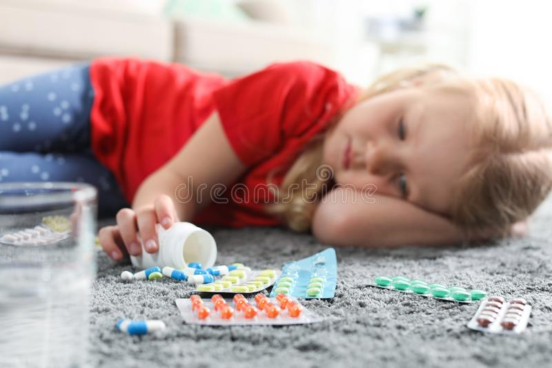 Little child with many different pills on floor. Danger of medicament intoxication. Little child with many different pills on floor at home. Danger of medicament royalty free stock image