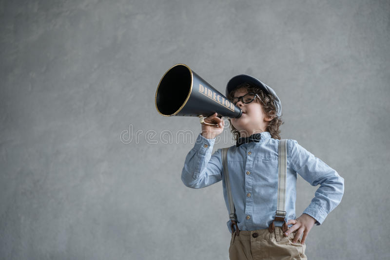 Little child. With a megaphone in studio stock photography