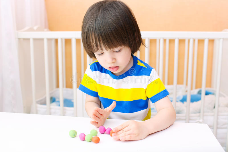 Little child modelling playdough balls stock photography
