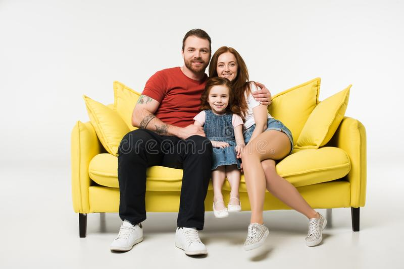 Little child between mother and father on couch royalty free stock photo
