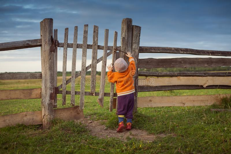 Little child opening  old gates. The storm approaching stock photos