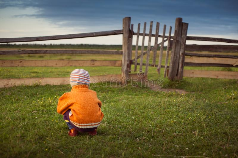 Little child opening  old gates. The storm approaching. Little child sitting and waiting someone near old gates. The storm approaching stock images