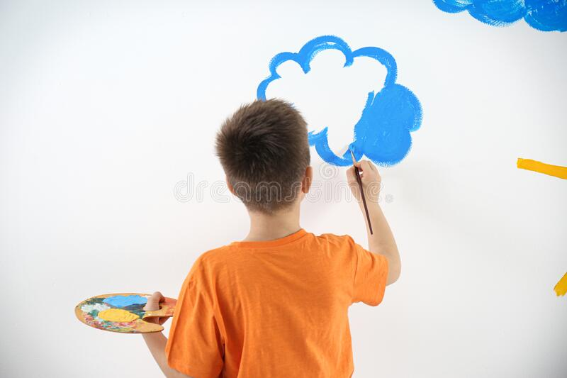 Little child painting cloud on wall in room stock photos