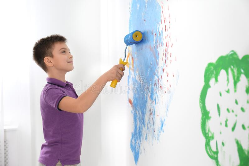 Little child painting wall with roller brush indoors royalty free stock photography