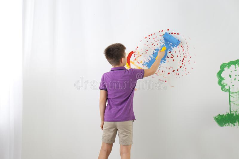 Little child painting wall with roller brush indoors stock photo
