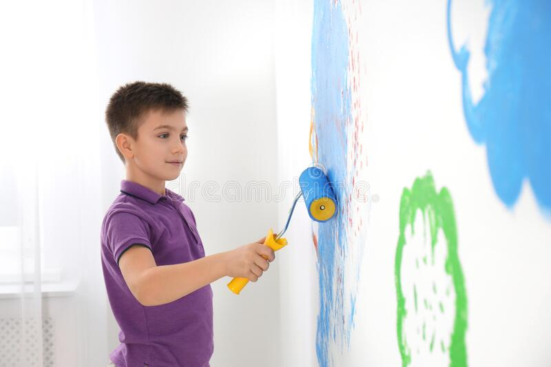 Little child painting wall with roller brush royalty free stock photography