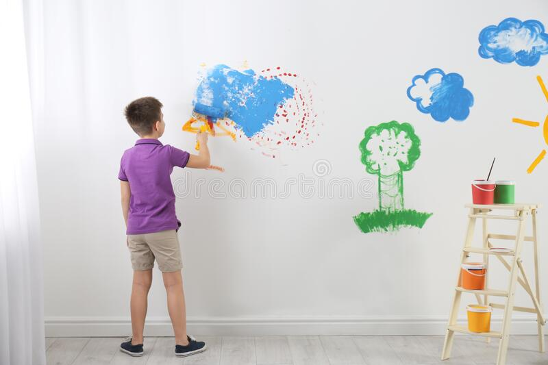 Little child painting wall with roller brush royalty free stock images