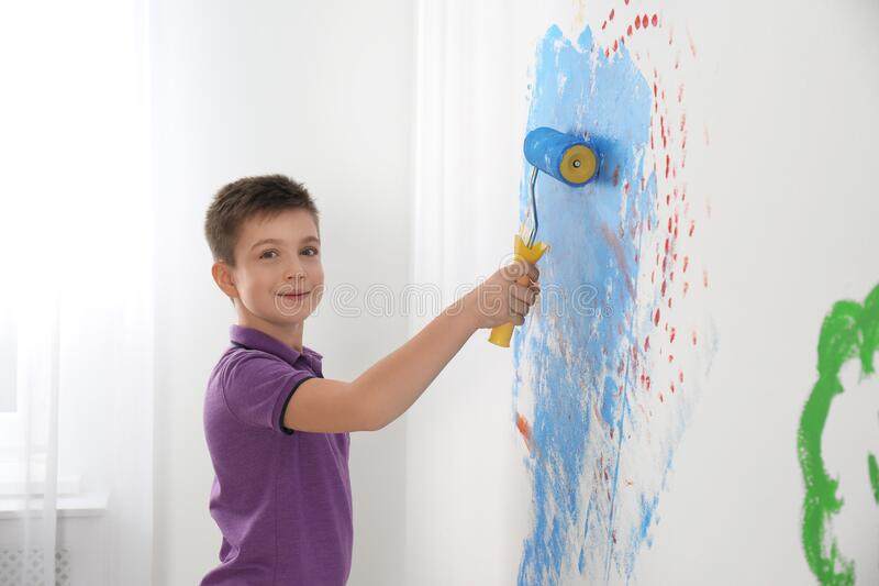 Little child painting wall with roller brush royalty free stock image