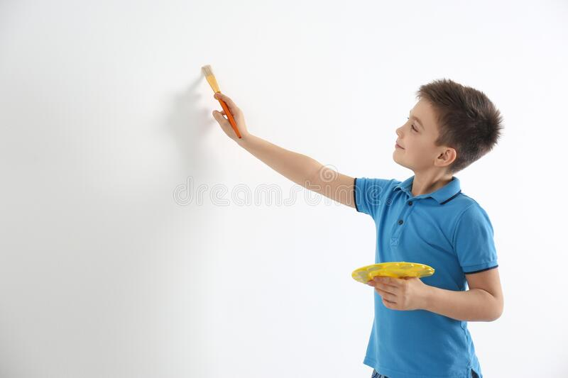 Little child painting on white wall indoors stock images