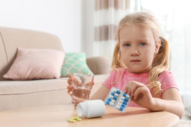 Little child with pills and water at table, space for text. Danger of medicament intoxication stock image
