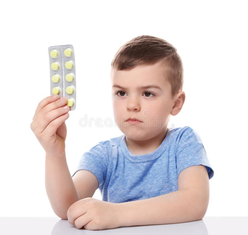 Little child with pills on white background royalty free stock photos