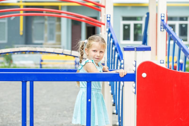 A little child on the playground. The concept of childhood, lifestyle, upbringing, kindergarten. A little child on the playground. The concept of childhood stock image