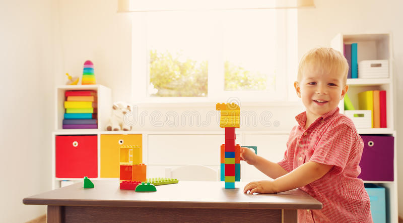 Little child playing with blocks. Boy sitting on the chair at table and building a house royalty free stock photography