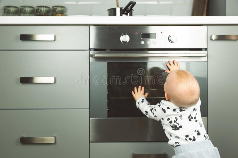 Little child playing with electric stove in the kitchen. Baby safety in kitchen stock images