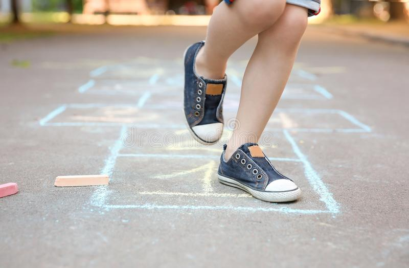 Little child playing hopscotch drawn with colorful chalk. On asphalt royalty free stock images