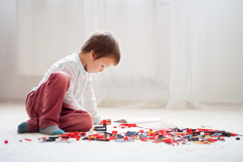 Little child playing with lots of colorful plastic blocks indoor. Building a fire truck and a fire house, reading from a manual and imagining royalty free stock image