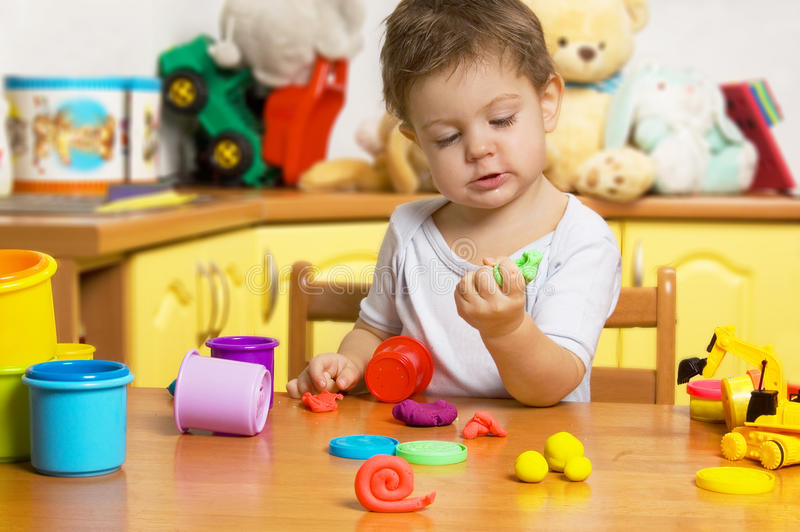 Little child playing plasticine stock photos