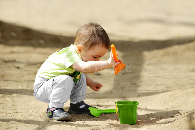Little child playing in sandbox stock images