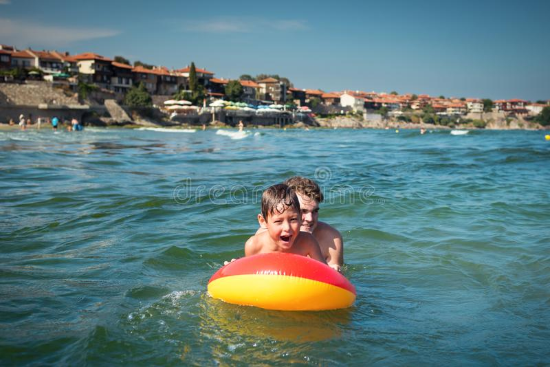 Little child playing in sea on inflatable mattress on waves with father royalty free stock photography
