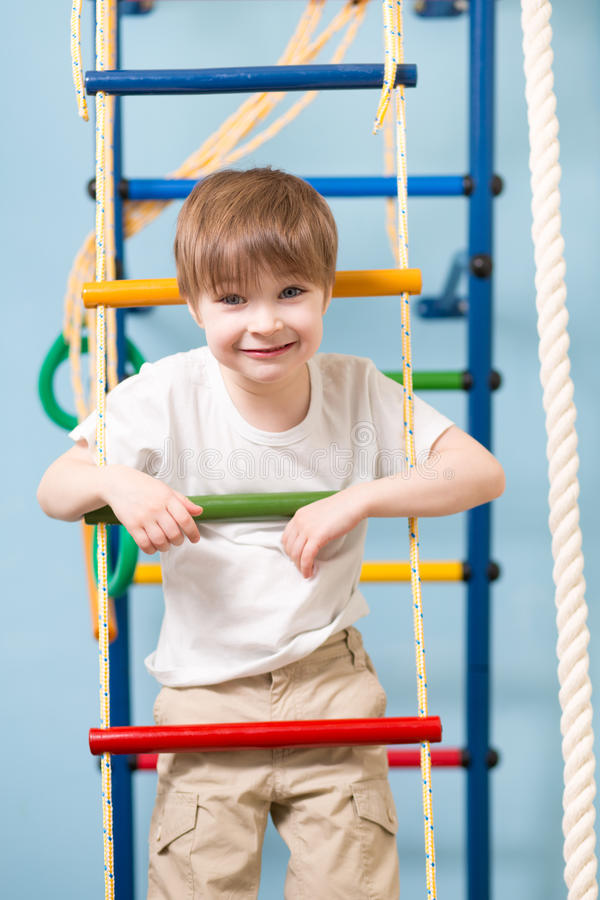 Little child playing sports at sport center. Kid boy standing on a rope ladder. stock image