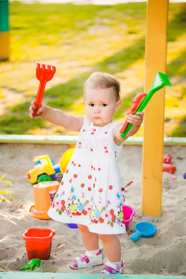 Little child playing with toys in sand on children playground royalty free stock photography