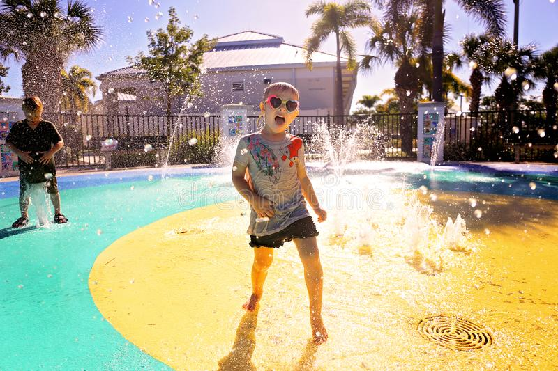 Little Child Playing in Water at Splash Park on Summer Day royalty free stock photography