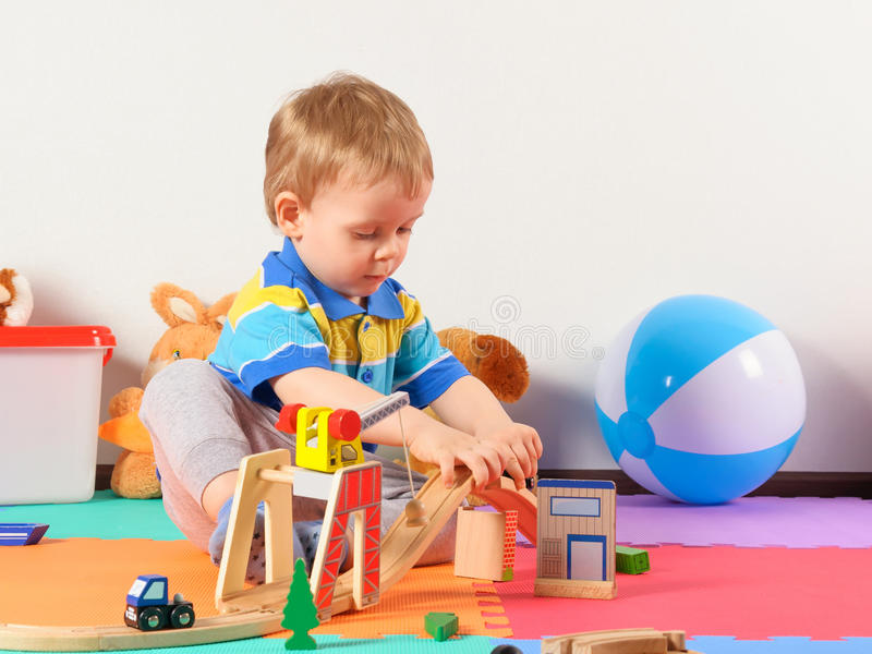 Little child playing with wooden railway. Little child playing with wooden railway on the floor stock images