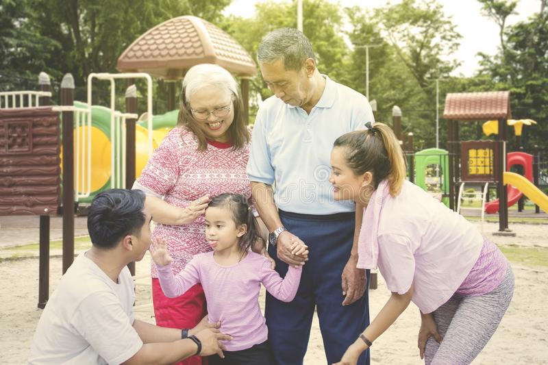 Little child plays with her family in the playground. Picture of little child looks happy while playing with her family in the playground royalty free stock photo