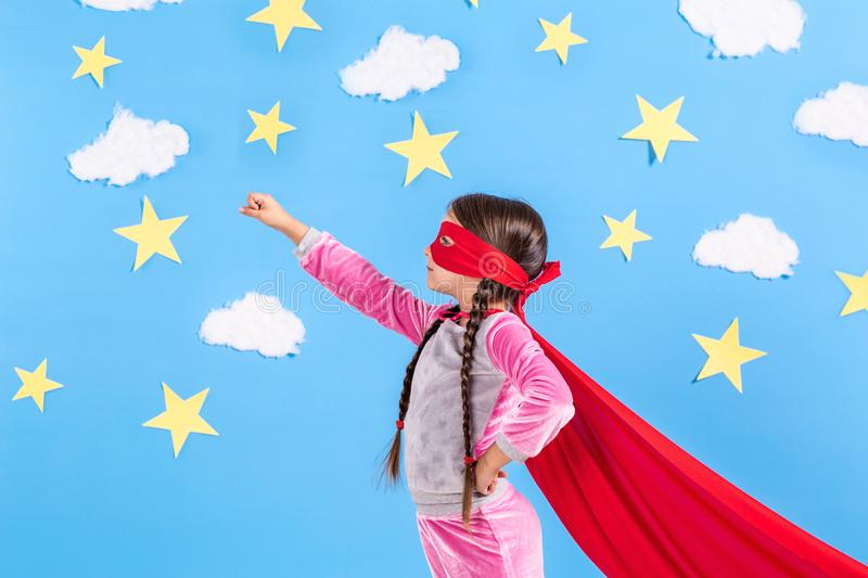 Little child plays superhero. Kid on the background of bright blue wall with white clouds and stars . Girl power concept royalty free stock images