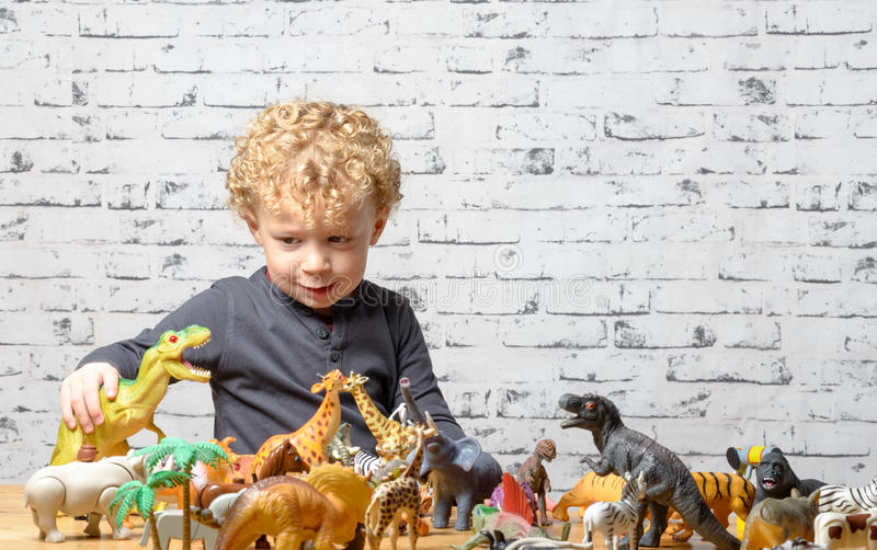 A little child plays with toys animals. And dinosaur stock photos