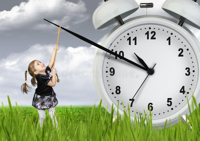 Little child pulling hand clock, time stop concept. Little child girl pulling hand clock, time stop concept stock photo