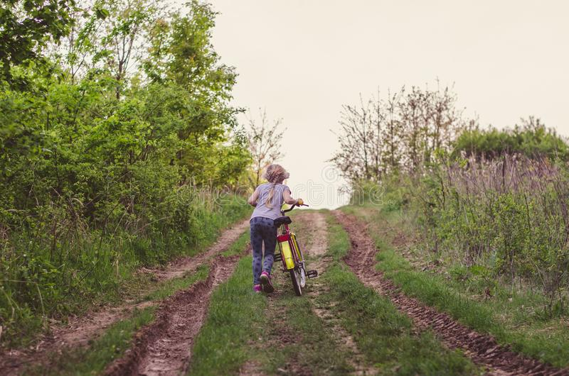 Little child pushing bicycle in the rural path royalty free stock photos