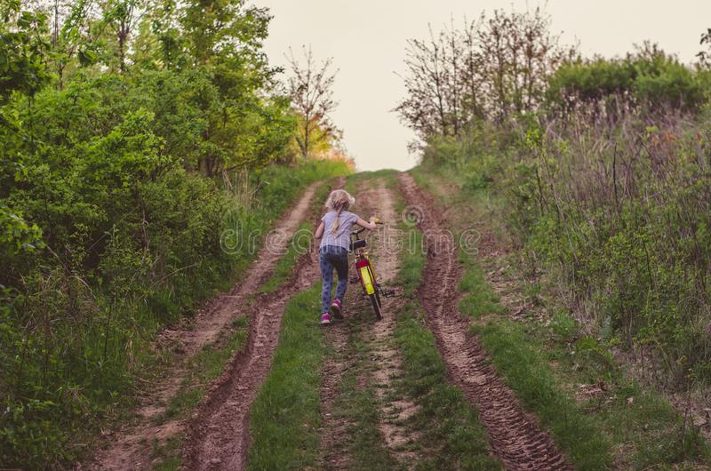 Little child pushing bicycleup to hill  in the rural path stock photography