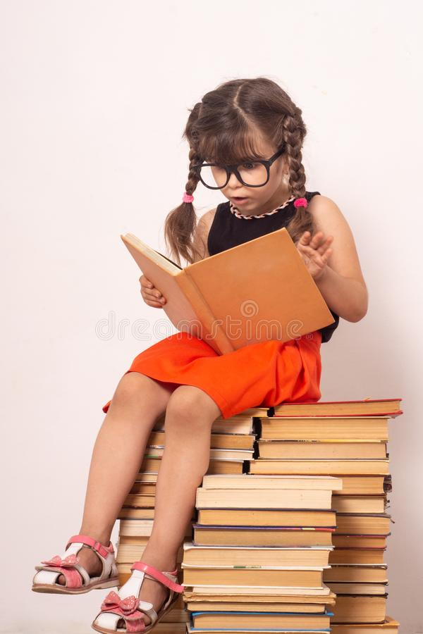Little child reading book and in bewilderment covers mouth. Kid with glasses sitting on books. royalty free stock image