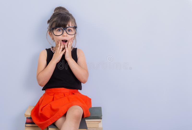 Little child reading book and in bewilderment covers mouth. Kid with glasses sitting on books. royalty free stock photos