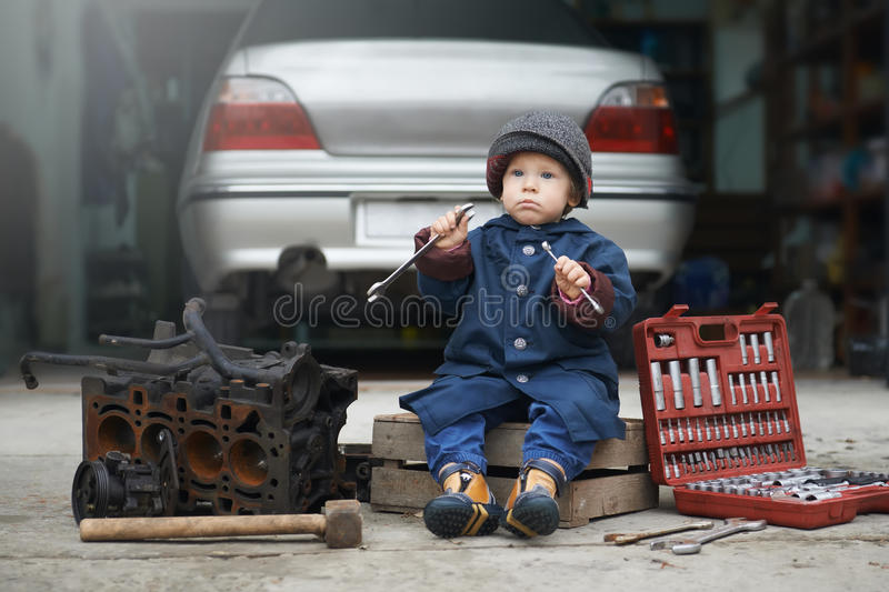 Little child repairing car engine royalty free stock photo
