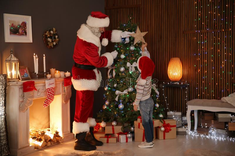 Little child with Santa Claus putting star on top Christmas tree at home stock images